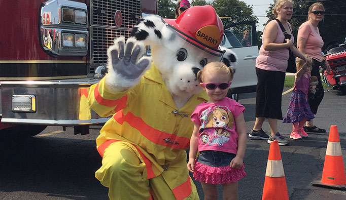 sparky mascot with child and firetruck