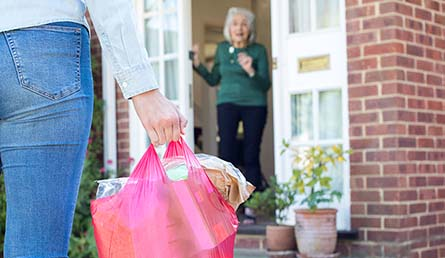 Image of young woman bringing bag of groceries to a senior from a distance
