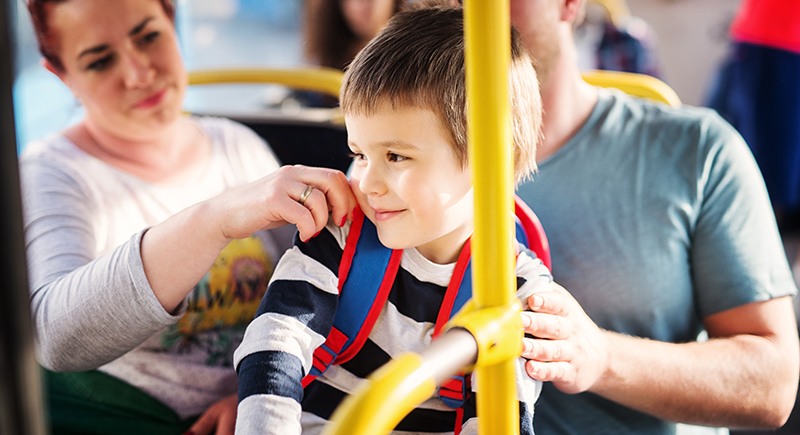 Boy riding a bus with his parents