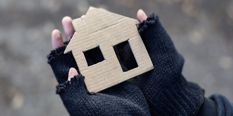 A pair of gloved hands holding a cardboard cut out of a house