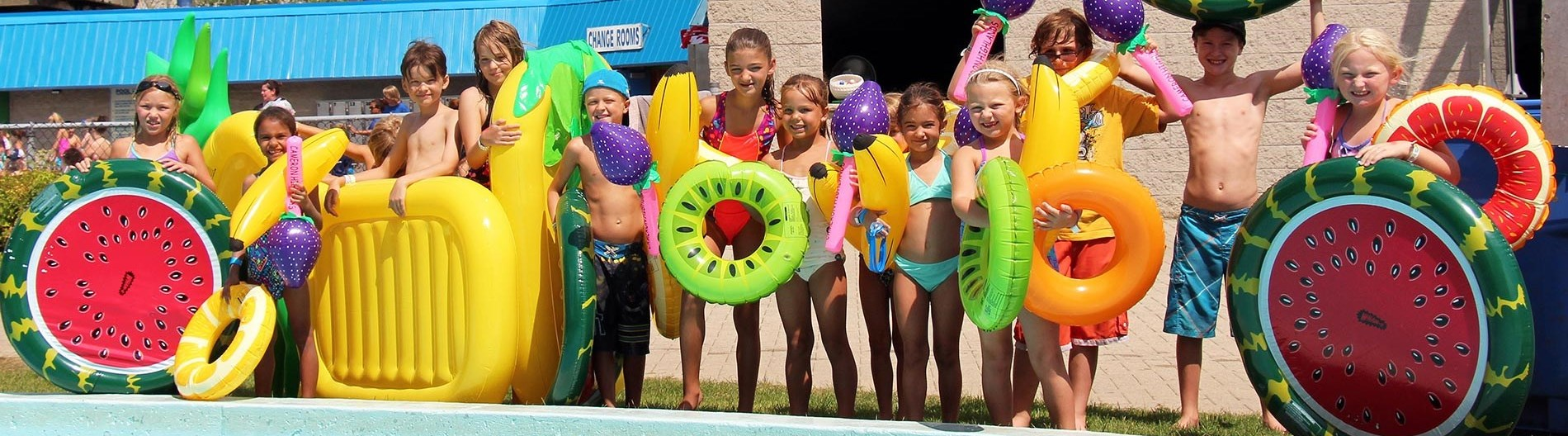A group of kids standing beside a pool at earl haig family fun park.