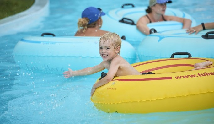 Small boy floating on lazy river at Earl Haig