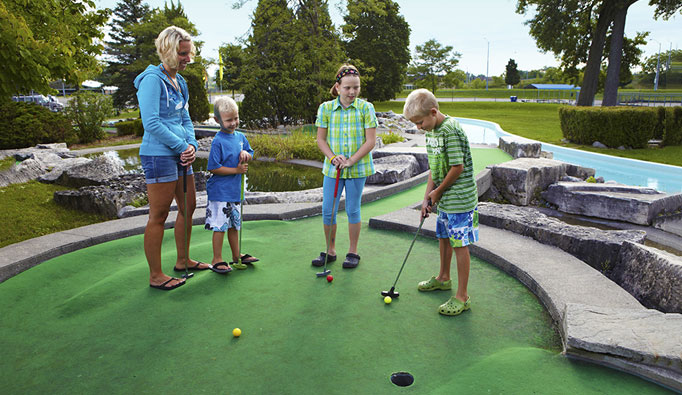 An adult and two children playing mini golf