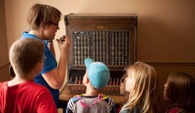 children looking at original phone switchboard